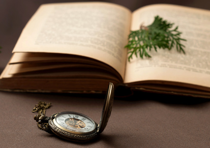 Old pocket watch with an opened book