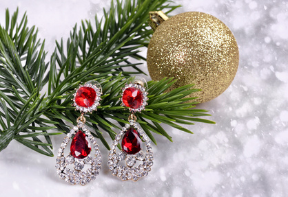 earrings with red stones on a branch of a Christmas tree with a ball on an abstract background