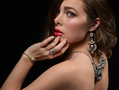 Portrait of young brunette woman with vintage silver diamond pendant jewelry and earrings on black background